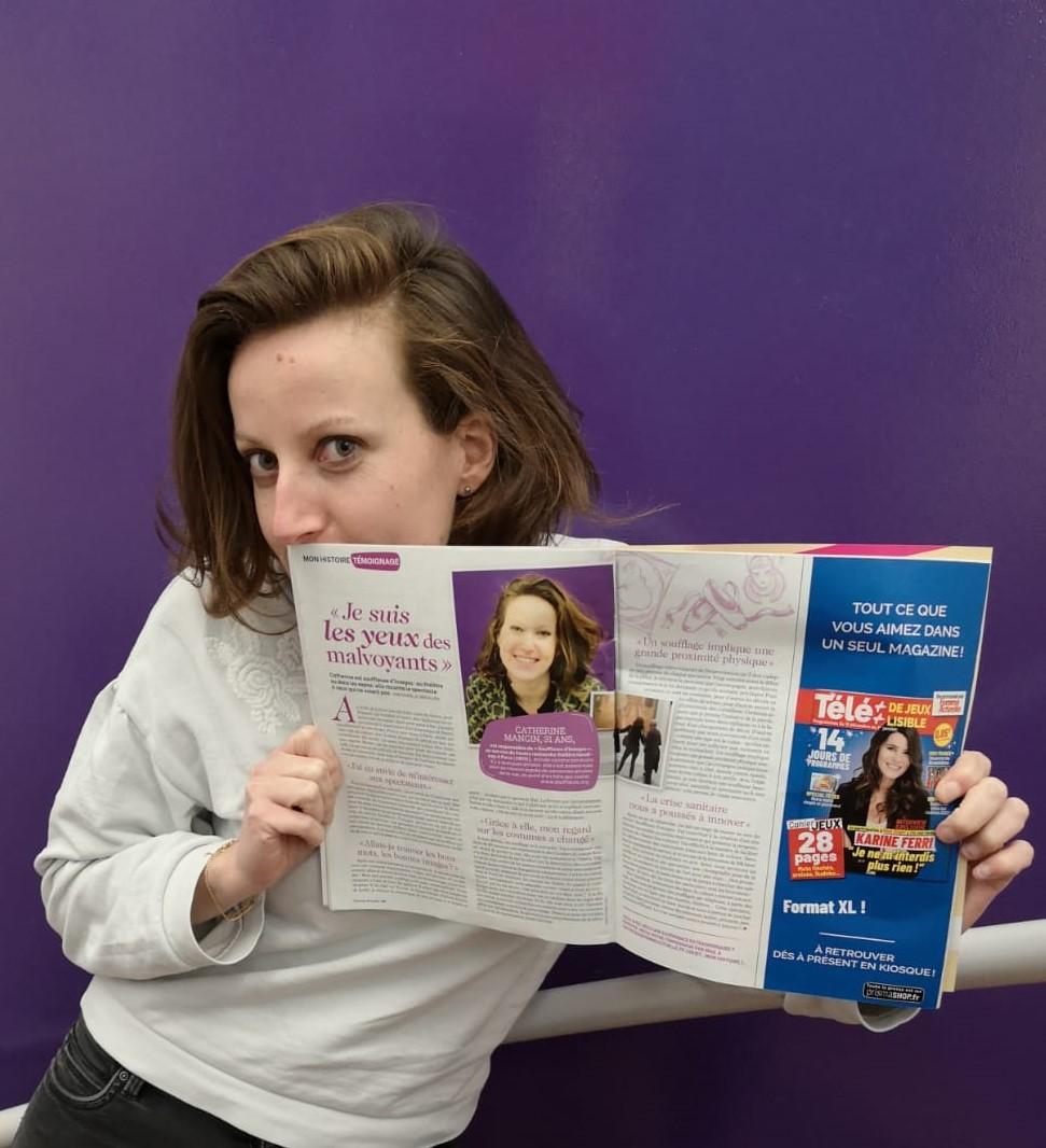 Catherine Mangin tient dans ses mains l'article de femme actuelle. Elle regarde l'objectif.