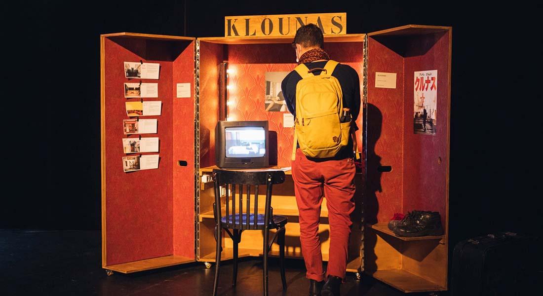 Photo d'une partie de l'exposition. Un jeune homme de dos observe une sorte d'armoire ouverte où s'entrepose à l'intérieur plusieurs éléments de l'exposition : des tableaux, une télévision,une chaise...